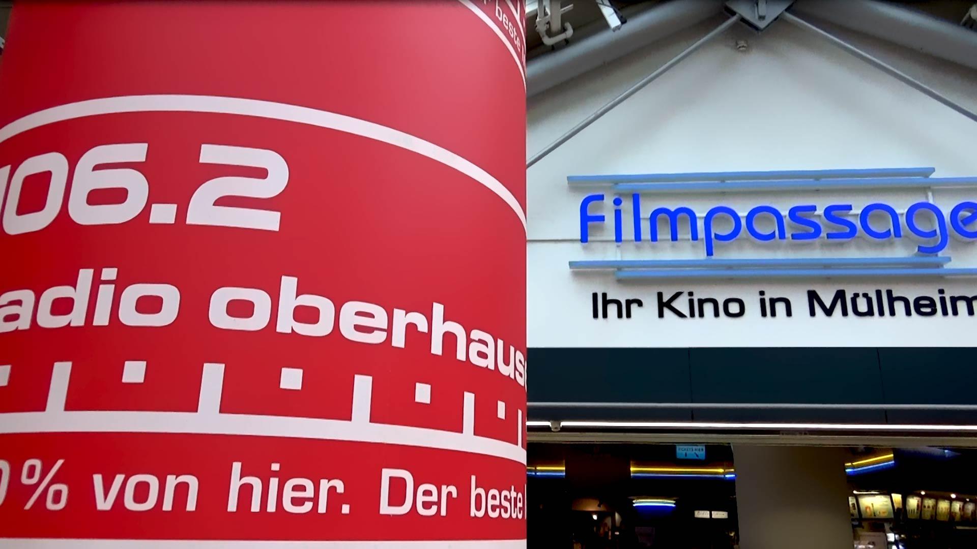 Foto der Filmpassage in Mülheim und im Vordergrund eine Leuchtsäule von Radio Oberhausen.