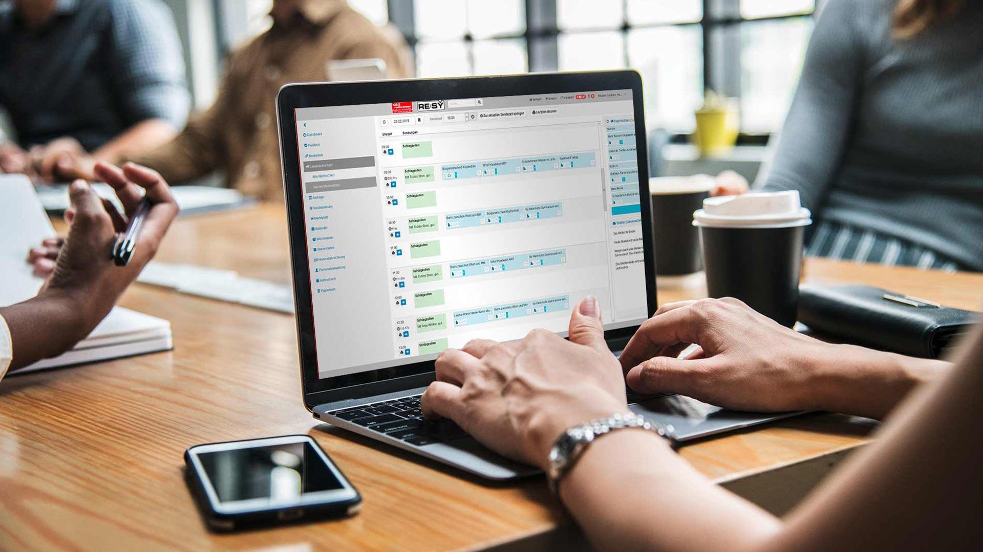 Foto einer Senderredaktion, auf welchem eine Redakteurin mit einem Laptop arbeitet und das Redaktionssystem ReSy geöffnet hat.