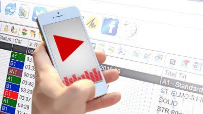 Eine Hand auf einem Smartphone, das einen Play-Pfeil anzeigt, schwebt vor einem Monitor mit der Software zur Planung der Webradios.