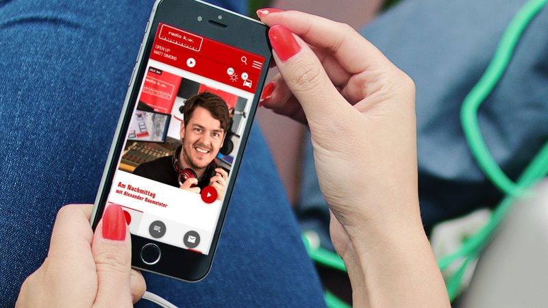 Eine Frau hält ein Smartphone mit geöffneter Website von Radio K.W. in der Hand.
