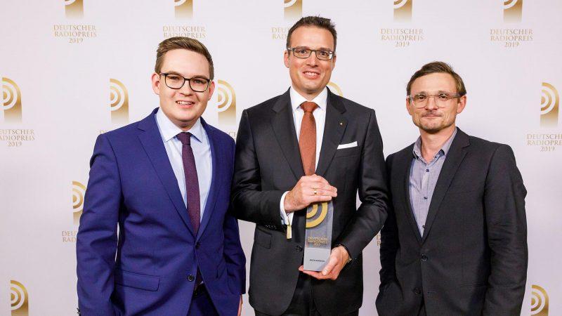 """Gewinner in der Kategorie """"Beste Sendung"""": Ralf Laskowski und Lennart Hemme von Radio Emscher Lippe mit Laudator Florian Lukas (r.). Bild: Deutscher Radiopreis/Morris Mac Matzen"""