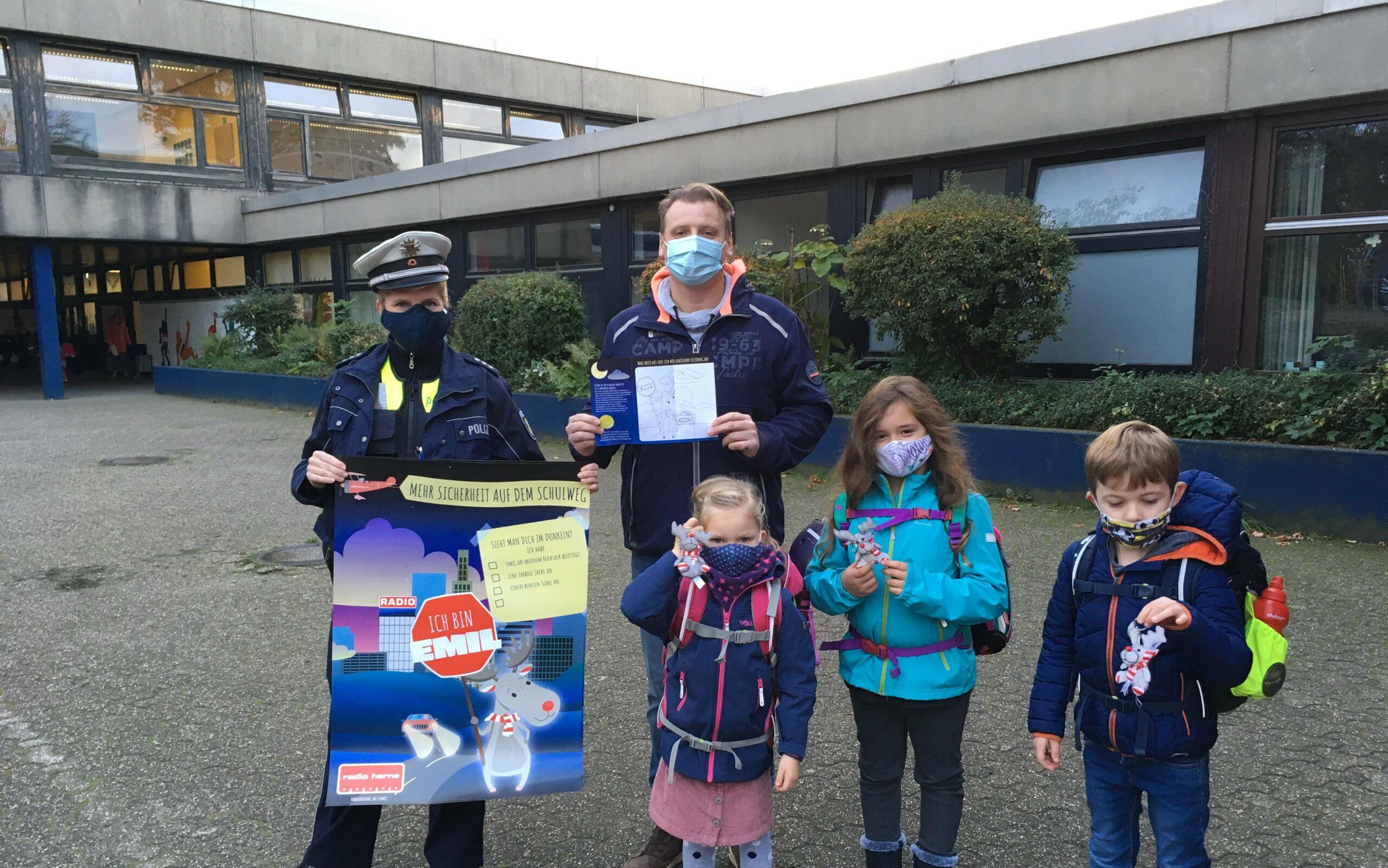 Die Polizei erklärt den Schülern anhand der Plakate die Bedeutung von reflektierender Kleidung. Foto: Radio Herne
